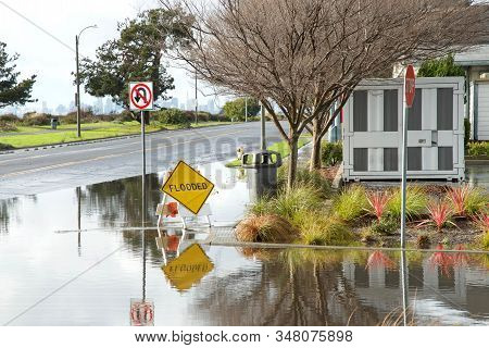 Intersection Submerged, Flooded After Recent Rains. Warning Signs Up To Prepare Drivers For Possibly