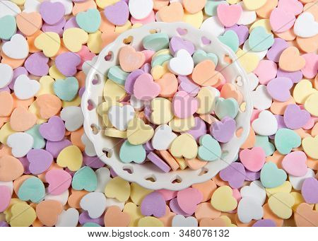 Flat Lay Top View Of A Small Porcelain Bowl With Heart Cutouts Holding Pile Of Large Pastel Candy He