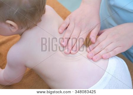 Professional Doctor Masseur Making Massage To Baby On Back In Clinic. Mom Playing Toy With Baby. The