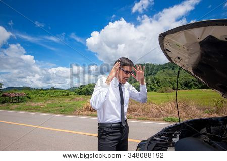 Frustrated Businessman With His Broken Car Looking In Frustration At Failed Engine.