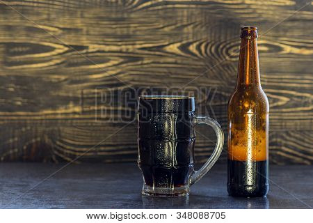 Wooden Background, Mug And Bottle Of Dark Beer With Foam. Copy Space. Close-up
