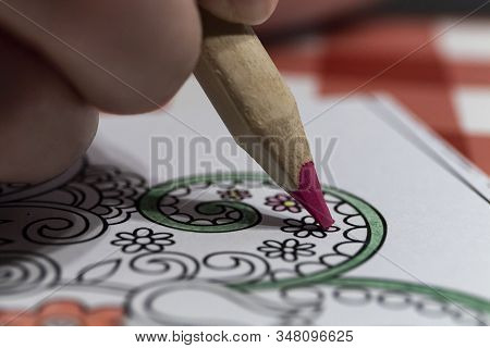 Close-up Of Someone Coloring In A Coloring Book With A Red Pencil. An Adult Coloring In A Coloring B