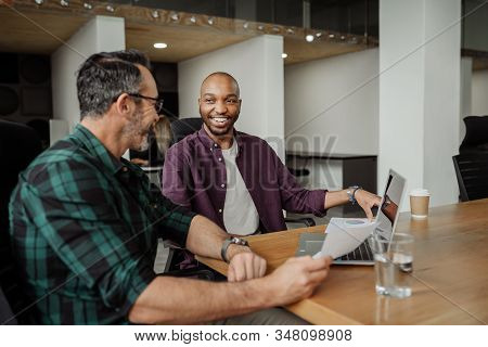 Two Diverse Businessmen Working In Modern Coworking Workspace. Candid Meeting