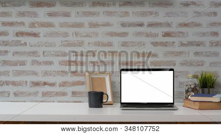 Cropped Shot Of Blank Screen Laptop, Mock Up Frame And Decorations On White Table With Brick Wall Ba