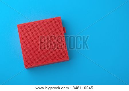 Red Portable Speaker With Usb Cable On Blue And Yellow Background With Space, Flat Lay