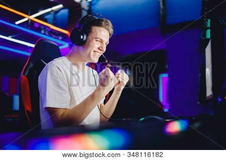 Streamer Young Man Rejoices In Victory Professional Gamer Playing Online Games Computer With Headpho