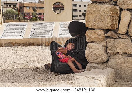 Muslim Woman Sits On The Ground In Paris And Holds A Sleeping Child In Her Arms. October 25, 2018. J