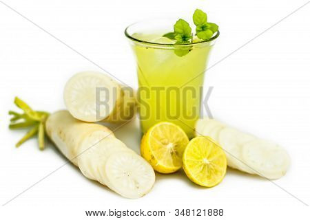 Close Up Shot Of Fresh Daikon Juice In A Glass Isolated On A White Background Along With Some Sliced