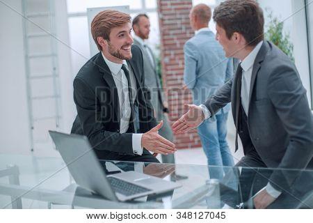happy business people shaking hands near the desktop