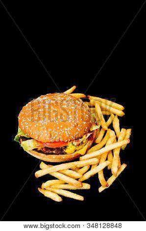 Hamburger and fries on black