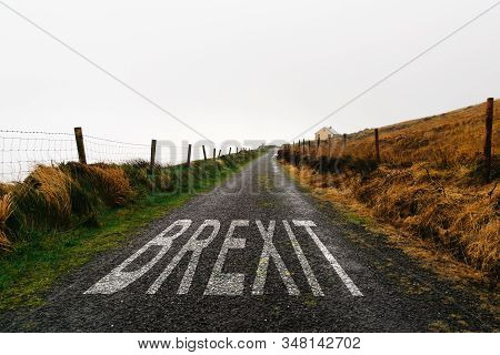 Concept Of Brexit.  Road Marking With The Word Brexit Painted On Remote Road A Misty Day. Concept Un