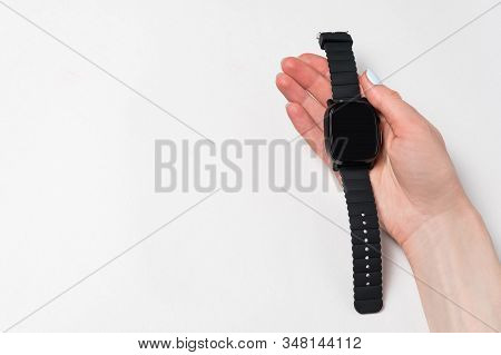 Female Hand Holding Smart Watch. Wrist Watch In Hand On White Background. Isolated, Copy Space.