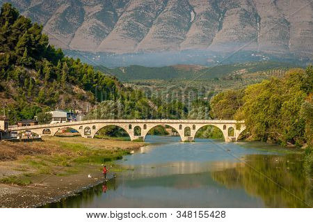 Berat, Albania On August 29, 2019: Gorica Bridge Over Osum River With Majestic Mountain In The Backg