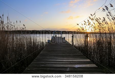 Old Wooden Pier At Small Beautiful Pond On Sunset