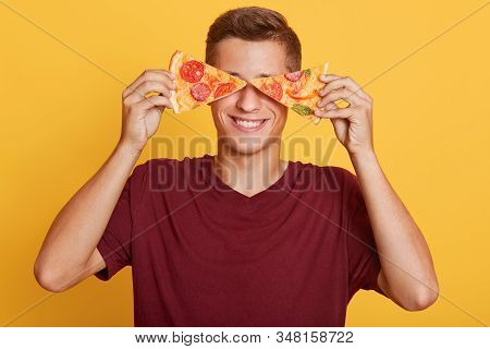 Image Of Cheerful Handsome Young Boy Holding Two Pieces Of Pizza In Both Hands, Having Beautiful Smi