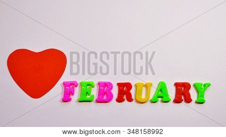 Big Red Heart And The Inscription February In Colored Letters On A Pink Background With Copy Space.