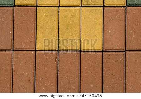 Group of multi-colored rectangular blocks. Cement blocks of different colors are laid tightly to each other with unfilled seams between them. View from above. Selective focus. poster