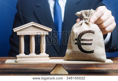 A Man Puts A Euro Money Bag On Scales Opposite To Government Building, Bank, University. Taxes Payme