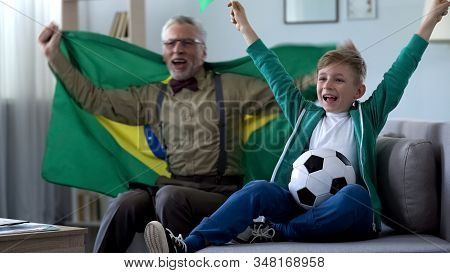 Granddad Waving Brazil Flag, Together With Boy Rejoice Victory Of Football Team