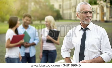 Handsome Professor Looking Into Distance Students On Background Higher Education