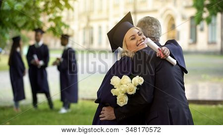 Father Hugging His Graduate Daughter Giving Flowers, Congratulating, Paternity
