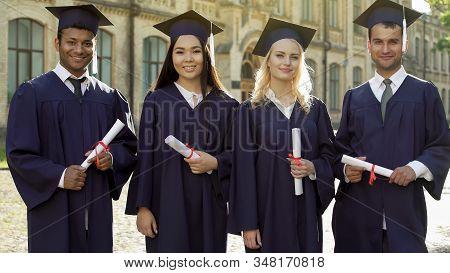 College Graduates In Academic Regalia Holding Diplomas, Celebrating Graduation