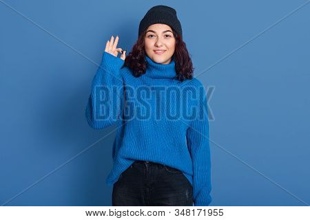 Indoor Picture Of Positive Cute Pleasant Brunette Making Gesture, Showing Sign Of Okay, Looking Dire