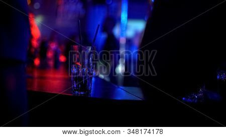 People Standing At Bar Counter And Waiting, Close-up Of Empty Glass, Nightclub
