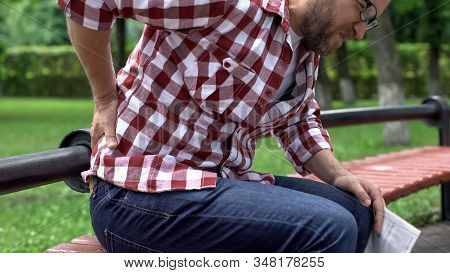 Man Feeling Lower Back Pain, Reading Newspaper In Park, Compressed Nerve Roots