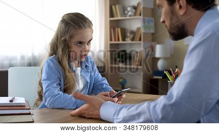Mischievous Daughter Playing On Smartphone Ignoring Dad, Family Conflict