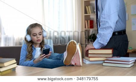 Disobedient Girl In Headphones Listening To Music On Smartphone, Ignoring Dad