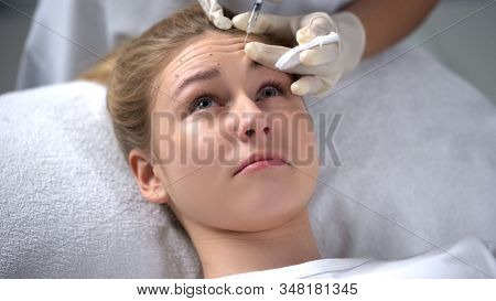 Professional cosmetologist making mesotherapy injection to young woman, beauty poster