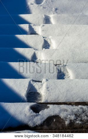 Footprints Of Boots On Snowy Steps. Stairs Covered With The Snow. Steps With Footprints In The Snow.