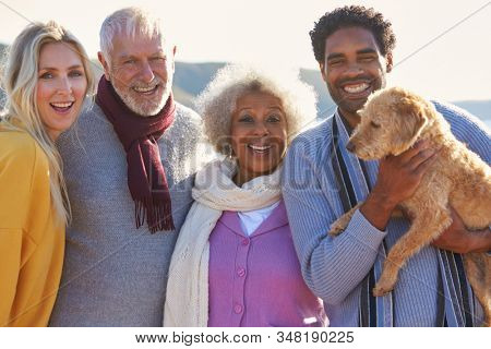 Portrait Of Senior Couple Walking Along Shoreline With Adult Offspring And Dog On Winter Beach Vacation