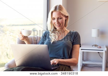 Woman Relaxing In Chair By Window At Home Using Laptop Drinking Coffee