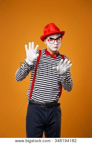 Mime looking at camera in vest and red hat Isolated on orange background