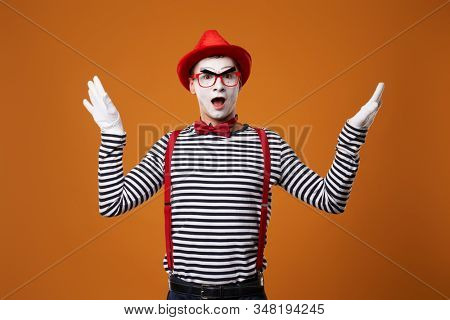 Surprised mime in red hat and vest showing thumb up on orange background