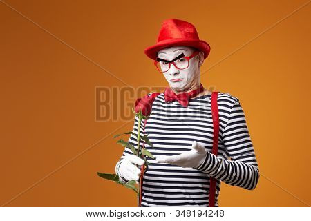 Serious mime in red hat and vest with rose in hands on orange background