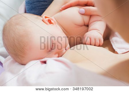 Mother Breastfeeding Her Newborn Baby In A Bed