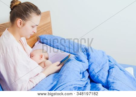 Woman Using Mobile Phone In Bed During Breastfeeds Newborn Baby