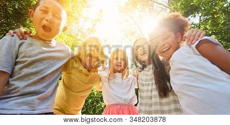 Multicultural kids have fun together in summer in nature