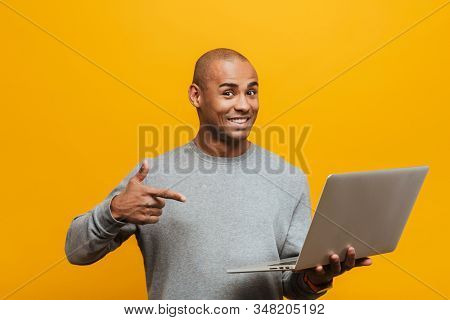 Portrait of an attractive smiling confident casual young african man standing over yellow background, pointing at laptop computer