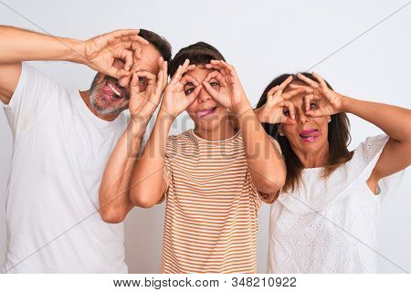 Family of three, mother, father and son standing over white isolated background doing ok gesture like binoculars sticking tongue out, eyes looking through fingers. Crazy expression.