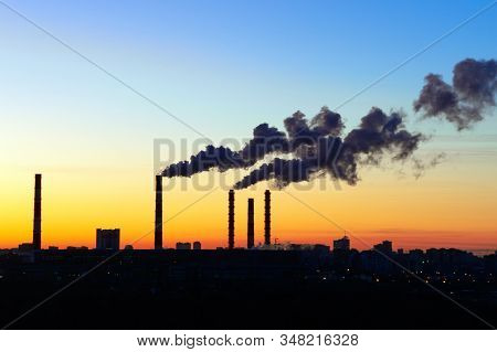 Pipes Smoke Factories At Sunset. The Silhouettes Of Factories And Factory Chimney Blowing Pollution