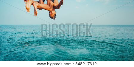 Young Man Jumping Off Cliff Into Blue Water Ocean At Sunset. Active Outdoor, Holiday Adventure, Tour