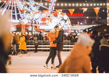 Beautiful Couple Ice Skating In City Centre. Young Couple Skating At A Public Ice Skating Rink Outdo