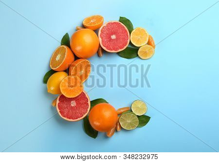 Letter C Made With Citrus Fruits On Light Blue Background As Vitamin Representation, Flat Lay