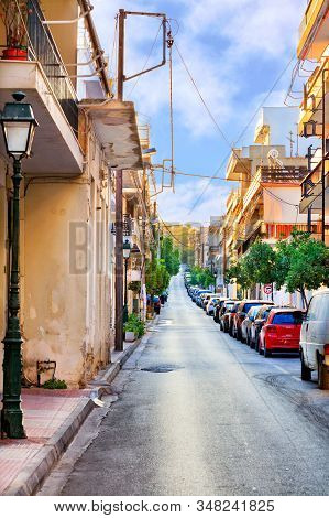 Narrow Carriageway Against A Background Of Parked Cars, A Deserted Street And Bright Morning Sunligh