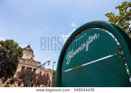 Welcome to Bloomington Indiana sign with downtown courthouse in background