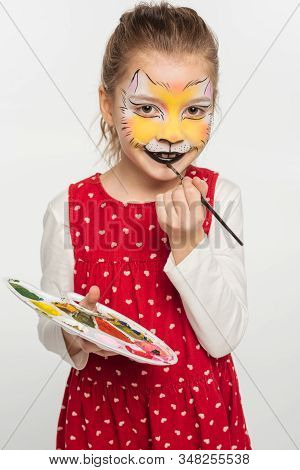 Smiling Kid With Tiger Muzzle Painting On Face Holding Palette While Painting On Lips With Paintbrus